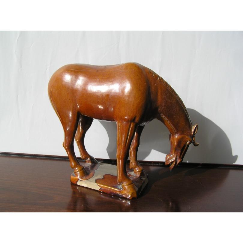 Petit cheval sur socle, tête baissée,