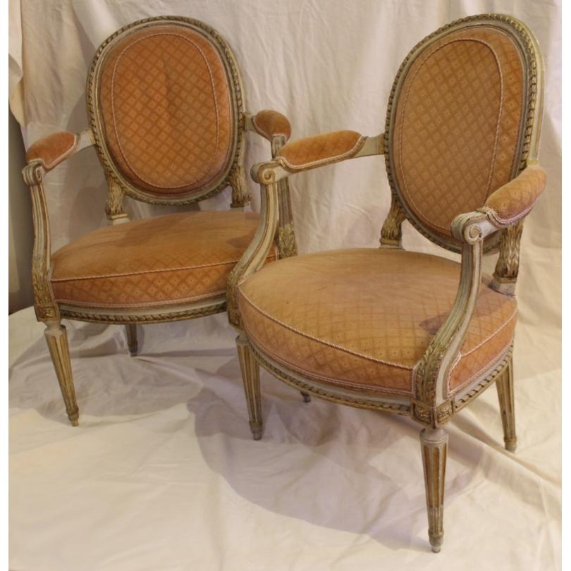 Paire de fauuteuils Louis XVI laqués blanc et or