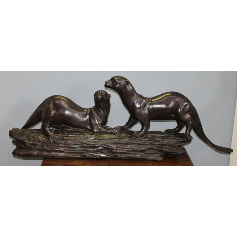 Couple de loutres sur une branche en bronze